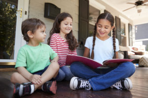 Group Of Children Sit On Porch Of House Reading Books